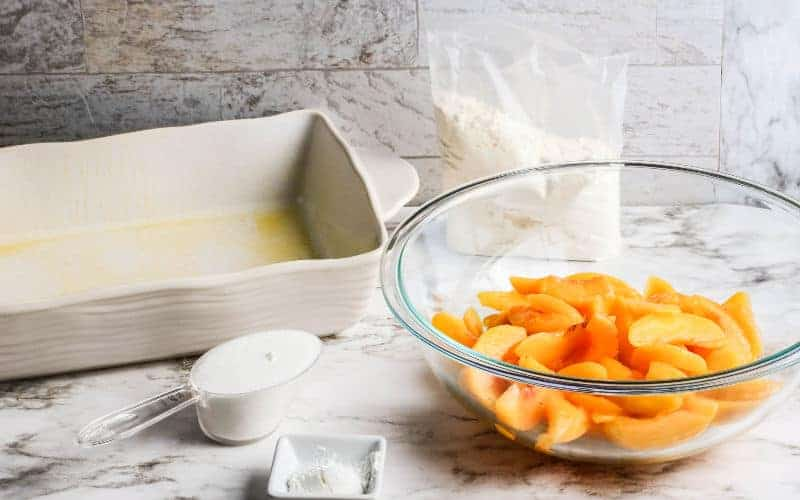 ingredients for a peach dump cake on table, peaches in bowl, casserole dish, sugar