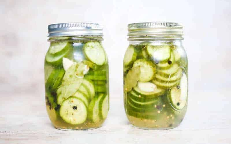 two pickled cucumbers in mason jars