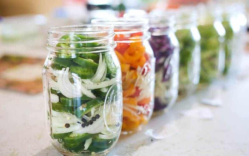 ball mason jars lined up with quick pickled jalapenos with onions and peppercorns in jar