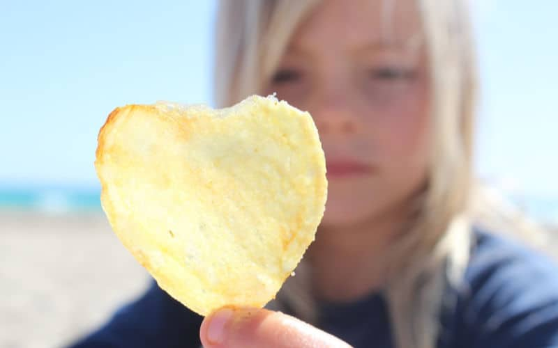 girl holding up chip at the beach as a beach food snack idea