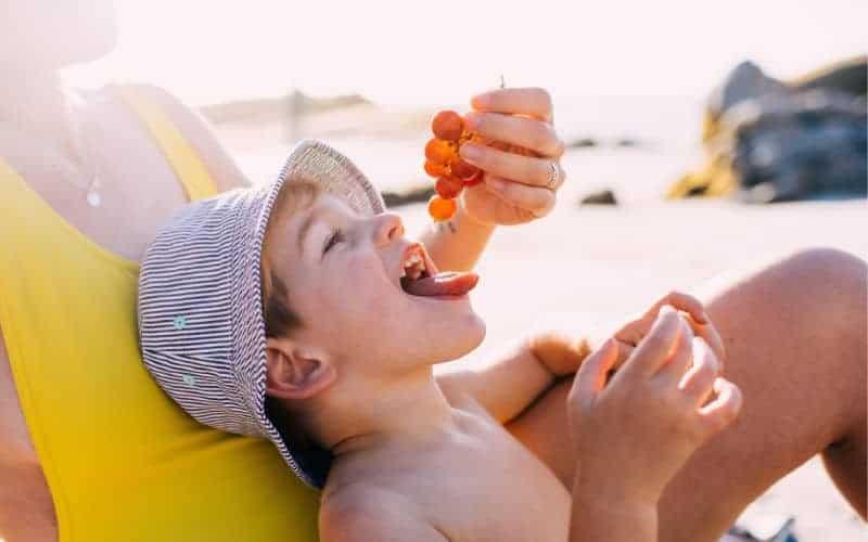 mom feeding little boy grapes on a beach beach snacks