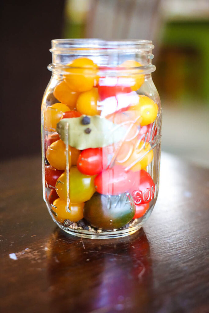 pickled cherry tomatoes in jar with spices