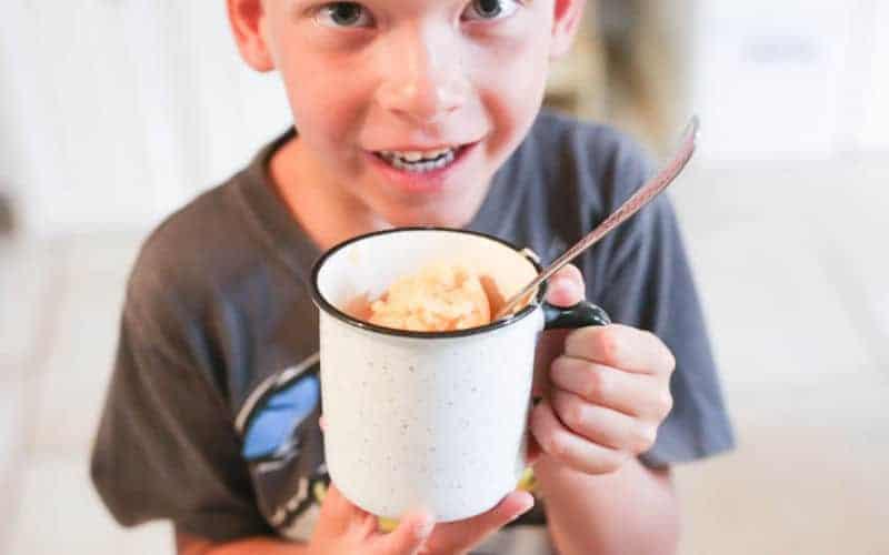 child holding white mug filled with orange pineapple churned ice cream