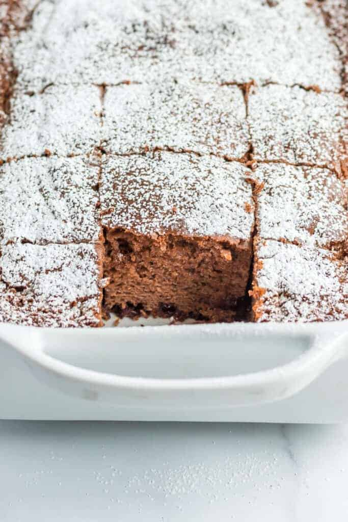 a chocolate chip cake with confectioners sugar in a casserole dish