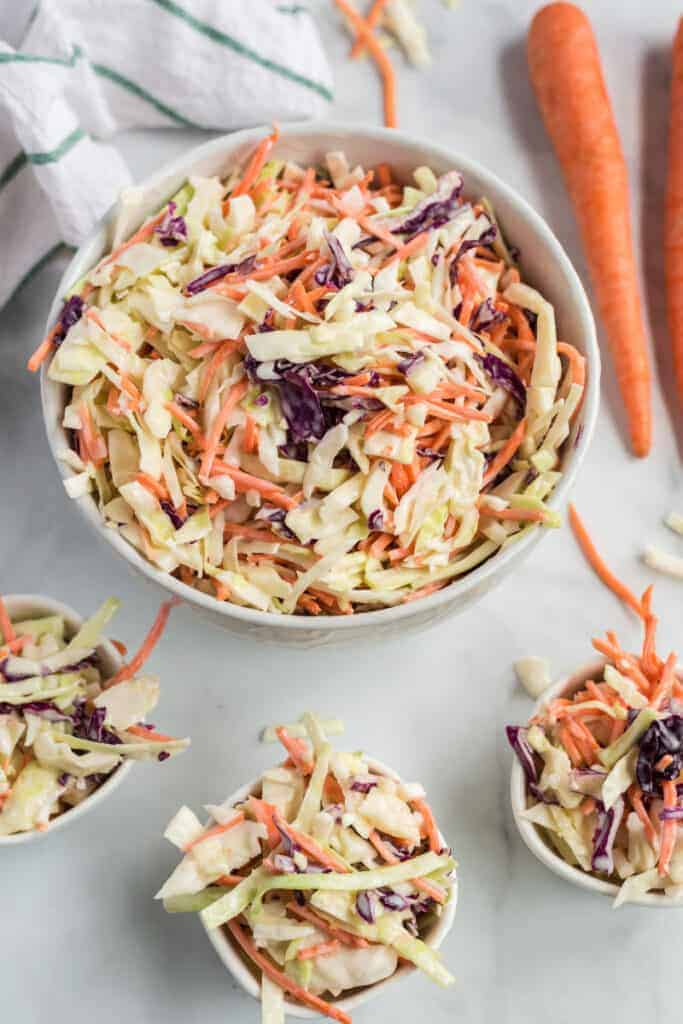 white and red cabbage and carrots in a bowl cole slaw