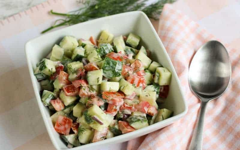 creamy cucumber salad with dill on a table with a spoon