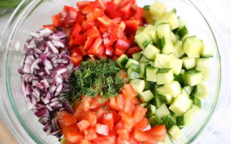 onions, peppers, cucumbers, dill, tomatoes, to make a cucumber salad