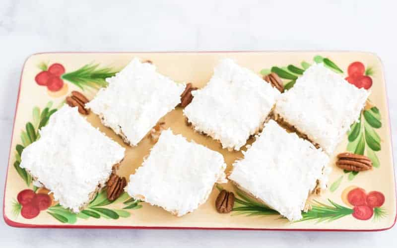 white Christmas cake cut in squares on a Christmas platter