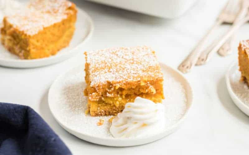 gooey pumpkin pie cake with confectioners sugar on a white plate