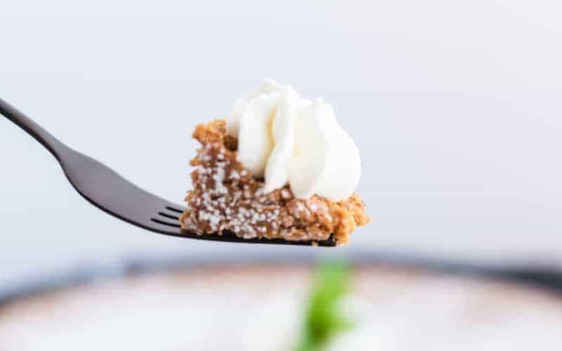 a fork holding a piece of syrup cake with cream on top
