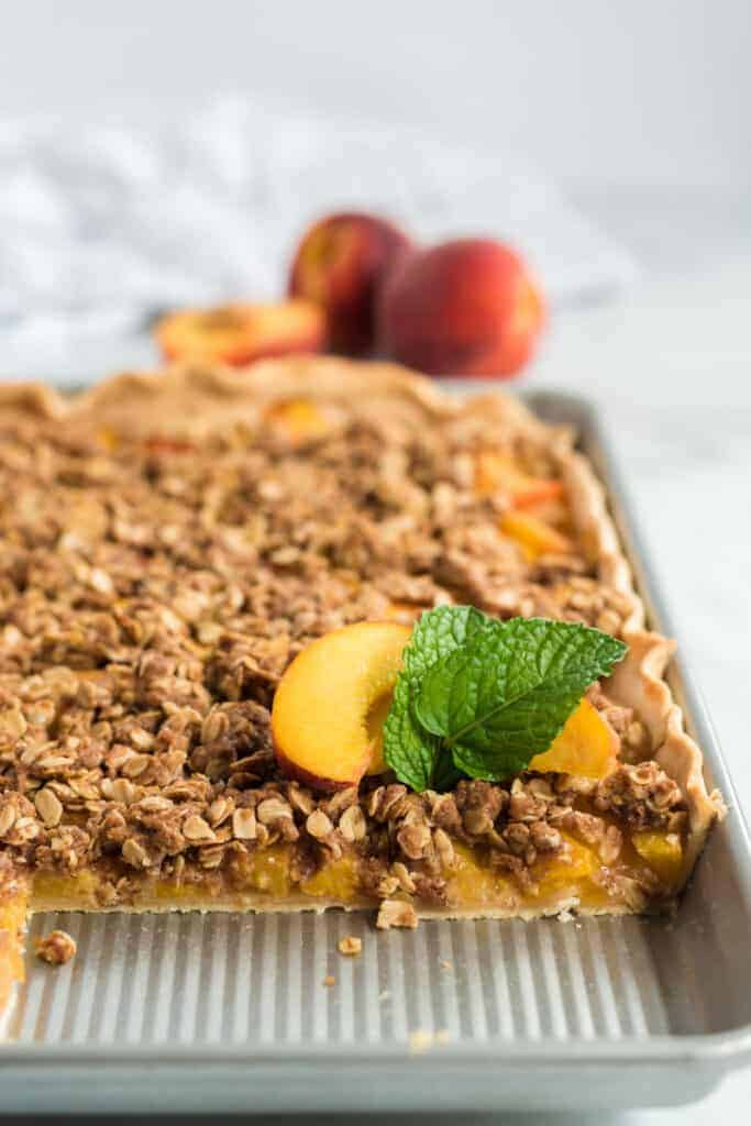 peach crumble slab pie in a jelly roll pan with peach on top