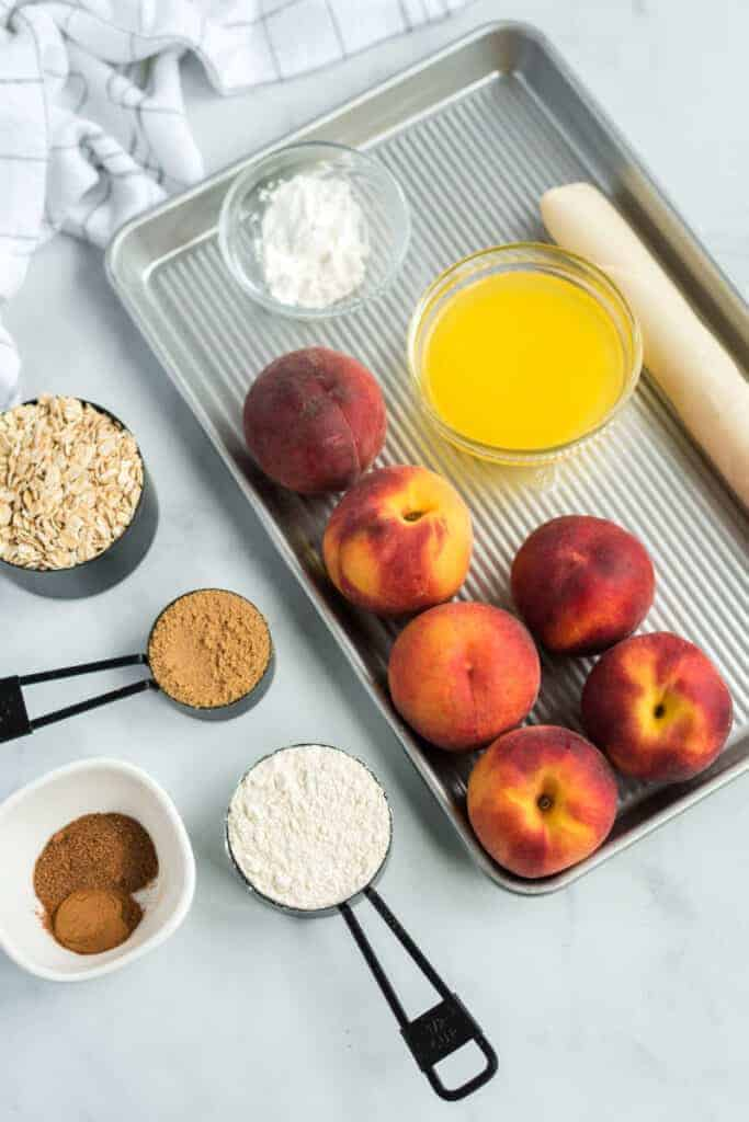 ingredients for peach slab pie on a jelly roll pan