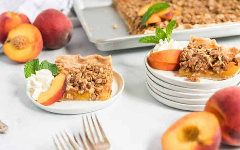 a peach crumble slab pie on a plate with peaches and cream
