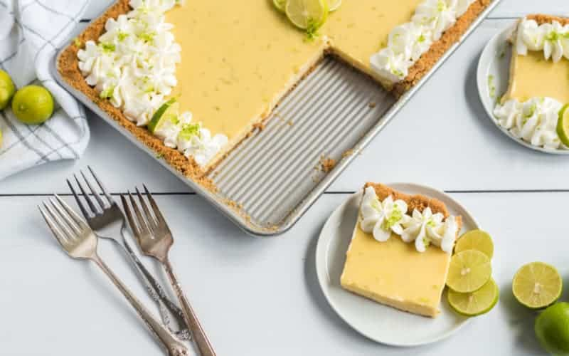 key lime slab pie with shipped cream and graham cracker crust on white table