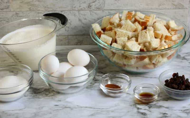 ingredients for bread pudding ont able, bread raisins cinnamon milk eggs sugar
