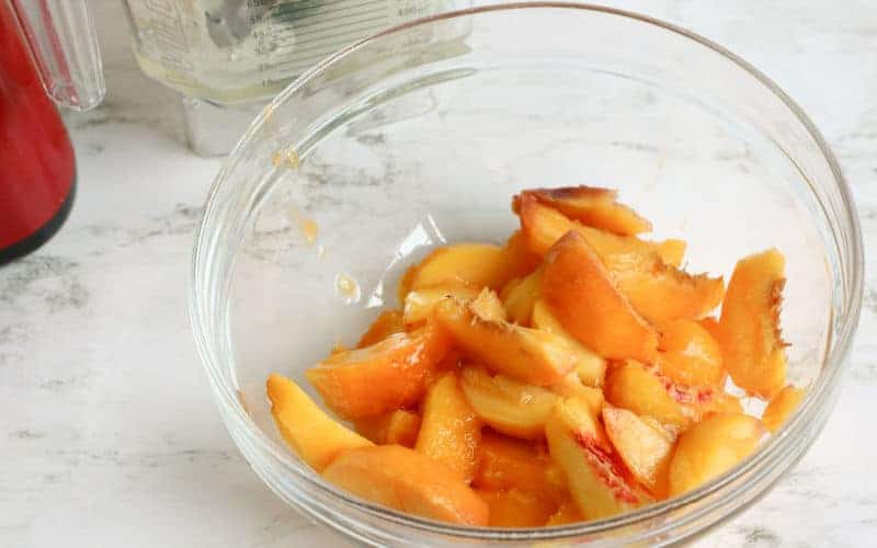 peaches in a clear bowl to be used for peach sorbet homemade ice cream