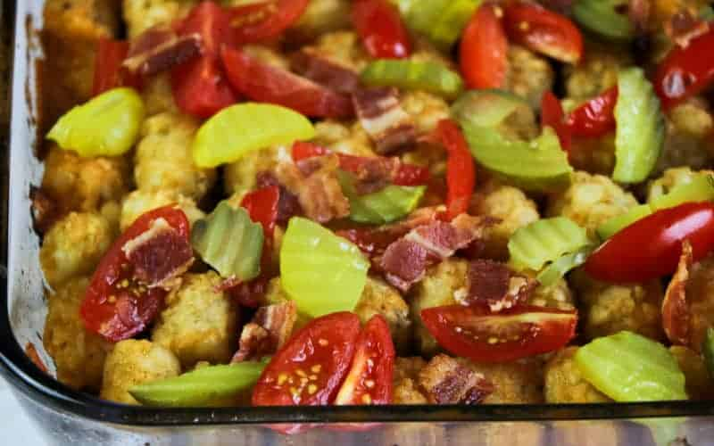 pickles and tomatoes on top of the bacon cheeseburger tater tot casserole